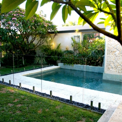 Small backyard pool with clear glass fencing