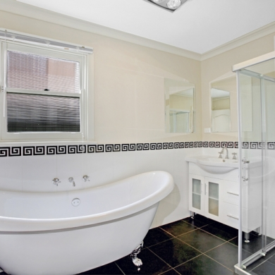 Bathroom with white walls and clawfoot bathtub