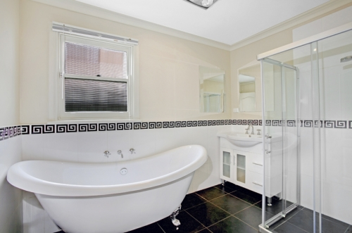 Bathroom with white walls and clawfoot bathtub