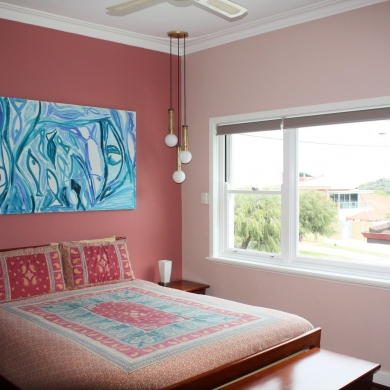 Pink bedroom with striking blue painting