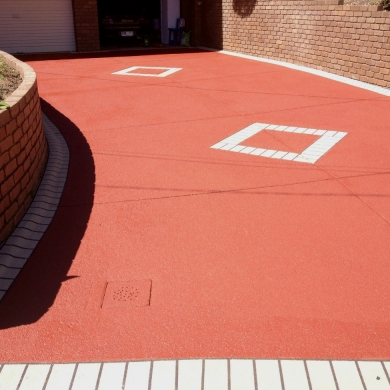 Striking coloured concrete driveway with design