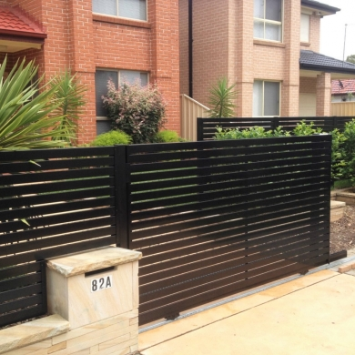 Black slat steel fence with a roller gate