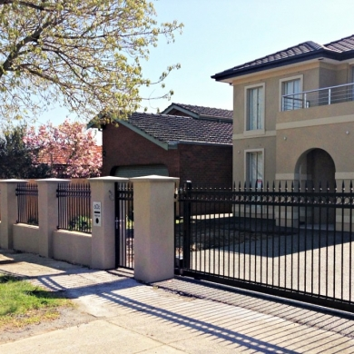 Black wrought iron fence with a roller gate