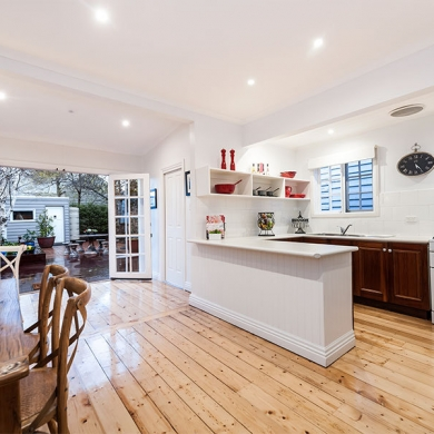 White and timber kitchen and dining areas with light timber flooring