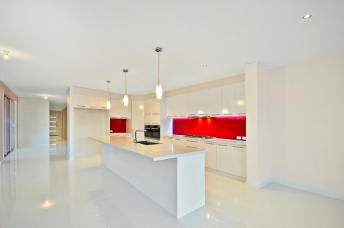 White kitchen with red splashback accent