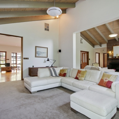 Fully carpeted living room with a high ceiling