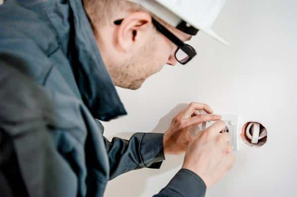 Electrician fixing wall socket