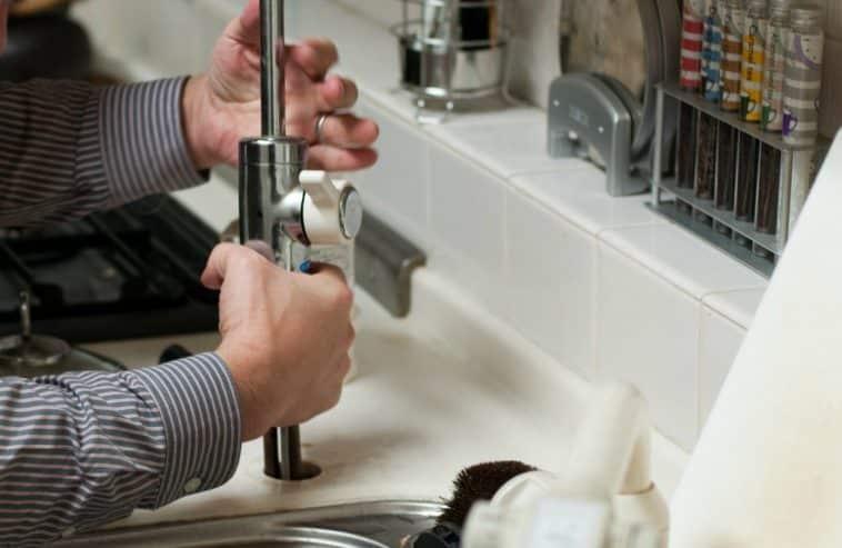 Plumber fixing broken tap