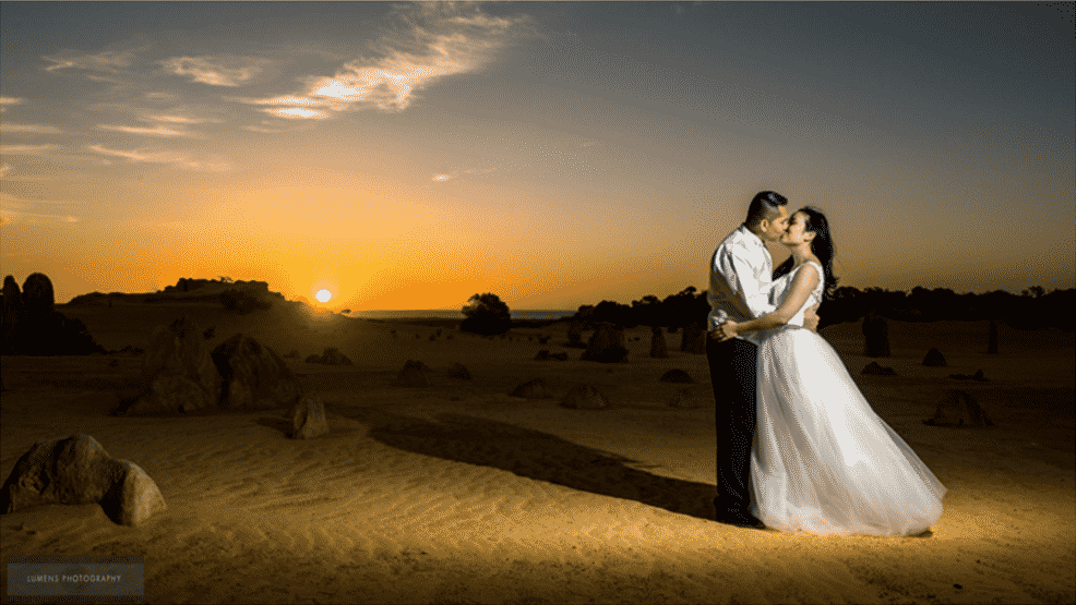 Bride and groom kissing sun setting
