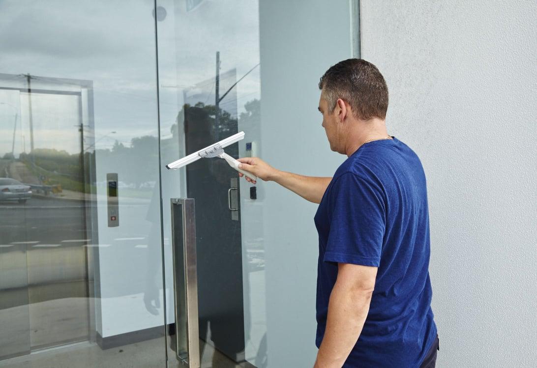 Tradie cleaning outdoors glass door