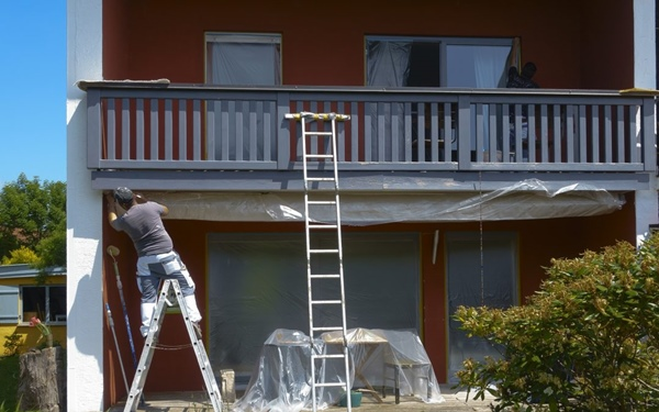 man repair the paint on the exterior