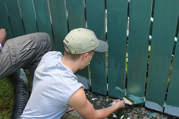men painting wooden fence