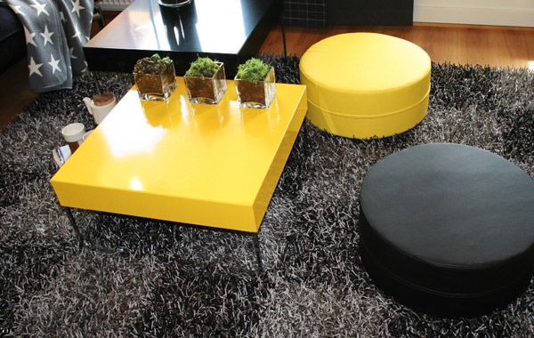 black and yellow round ottomans and yellow coffee table